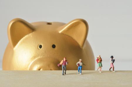 run away: miniature people run away from gold piggy bank