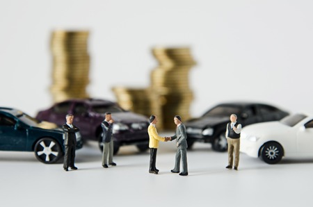miniature businessman team agreement with stack of coins background