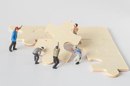 Miniatur-Arbeiter Team versuchen Puzzle zu vervollständigen