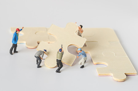 miniature worker team try to complete jigsaw puzzle