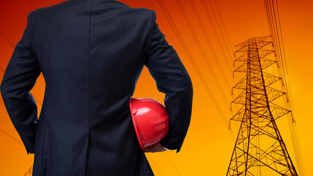 man in suite: business man in black suite holding red safety helmet with construction site background Stock Photo