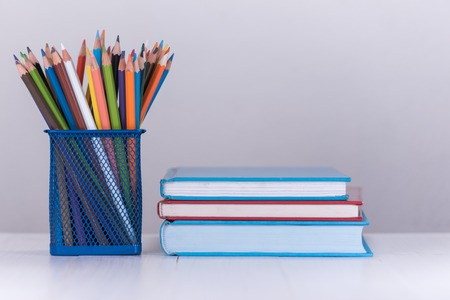 pencil box: color pencil box and stack of book on wooden table