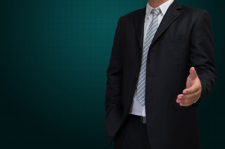 man in suite: business man with welcome hand in black suite on green background