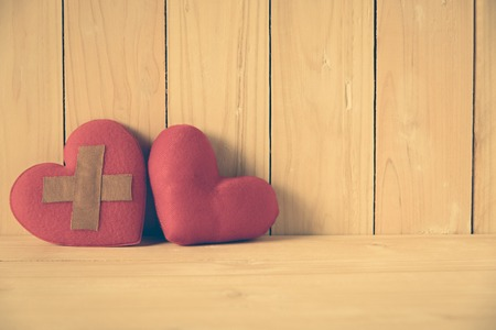 wound heart and red heart on wooden table