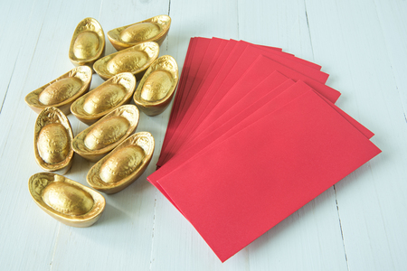 chinese golden ingots and red envelope on wooden table chinese new year theme stock photo