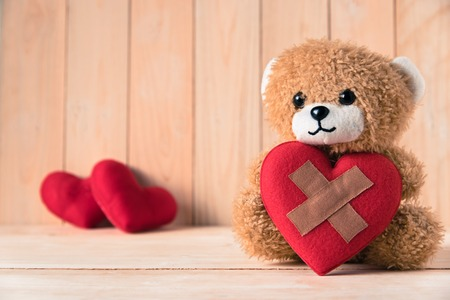 teddy bear holding wound heart with couple red heart background Stock fotó