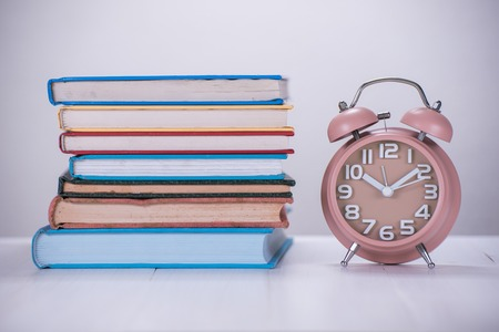 ten empty: brown alarm clock and stack of book on wooden table