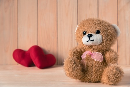 teddy bear with couple red heart background  on wooden table Stock fotó
