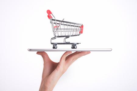 Warenkorb und Tablette auf der Hand Frau isoliert auf weißem Hintergrund