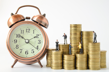 miniature people: business miniature people and clock on stack of coins