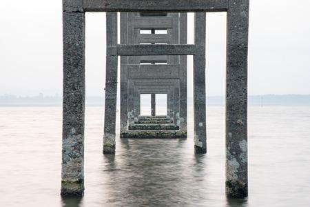torres de alta tension: La simetría de los pilones, una larga exposición en el muelle