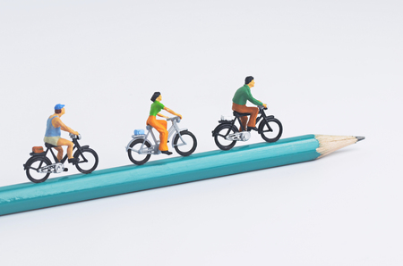 miniature people: Miniature people cycling on pencil