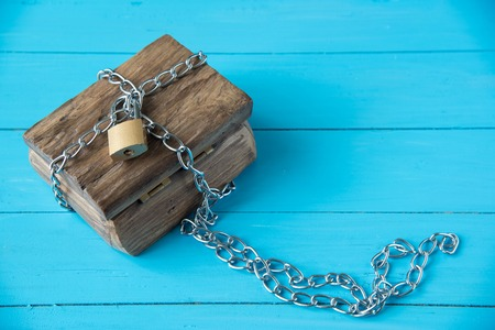 Holzschatzkiste auf blauem Holz Hintergrund Vorhängeschloss verriegelt