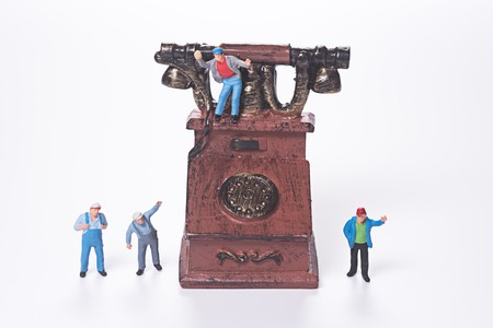 miniature people: miniature people and vintage telephone on white background Stock Photo