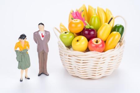pareja en miniatura con cesta de frutas sobre fondo blanco