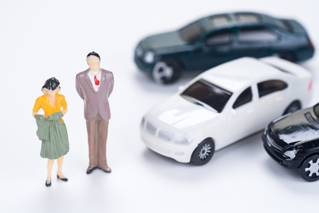miniature people: couple of miniature people with many car on white background