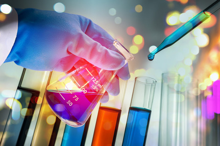 Double exposure of scientist hand holding laboratory test tube