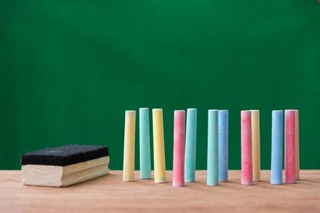 gessi in una varietà di colori e pennello sul tavolo con sfondo verde, torna al concetto di scuola