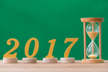 gold wooden font year 2017 and sandglass on wood table Stock Photo