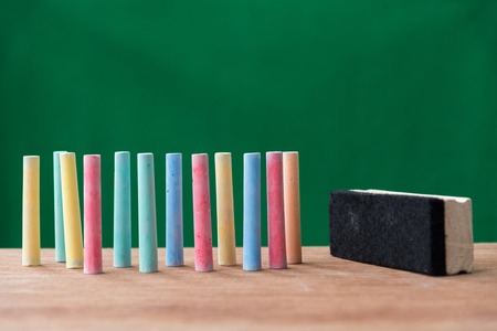 chalks: chalks in a variety of colors and brush on table with green background ,back to school concept