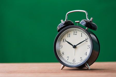 black alarm clock on wooden table with green background