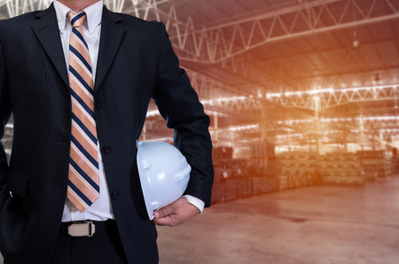 business man in black suite holding white safety helmet on construction materials warehouse background