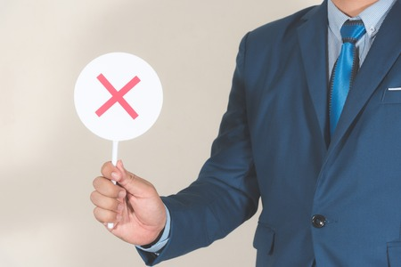 business man holding small white circle board with false sign