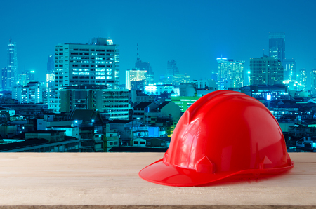 red safety helmet with night modern city building background