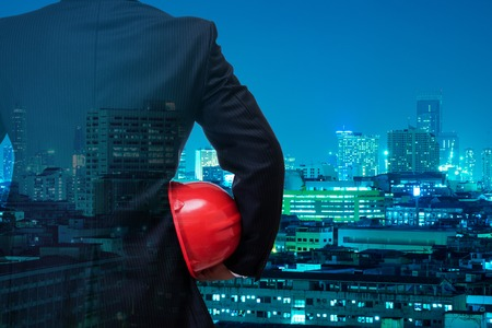 double exposure of business man in black suite holding red safety helmet with night modern city building background