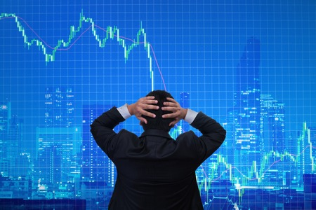 businessman shock when business graph going down with modern city background , business fail investment concept