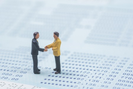 business miniature people shaking hands on book bank background