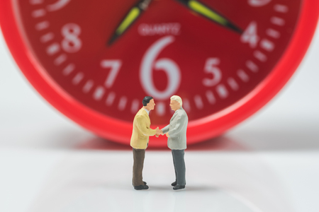 business miniature people shaking hands on alarm clock background