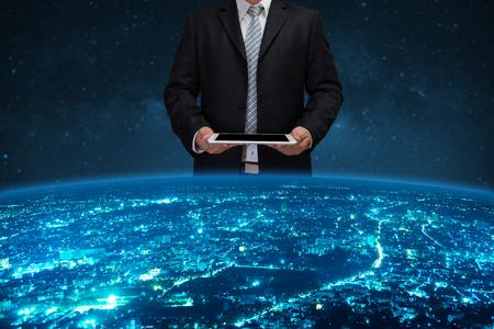 타블렛을 사용하는 검은 스위트의 사업가는 세계를 통제합니다.