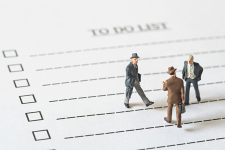 business miniature figures people walking on to do list