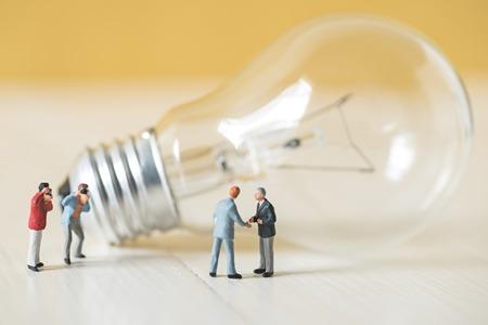 banco mundial: business miniature people make handshaking agreement with light bulb background Foto de archivo