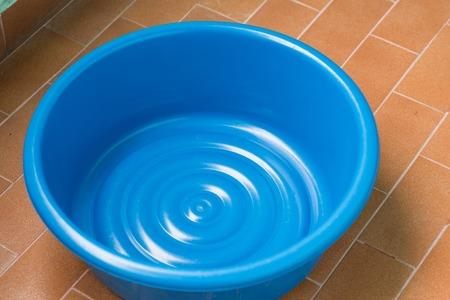 床に空青いプラスチック洗面器 写真素材