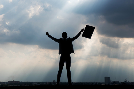 silhouette of businessman with document bag in hand raise arms up because success in business 版權商用圖片