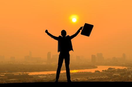 silueta de empresario con bolsa de documentos en mano levantar los brazos porque el éxito en los negocios