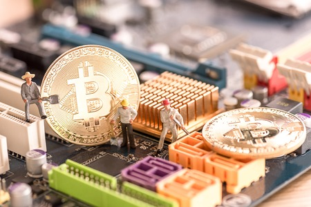 miniature people worker digging bitcoin on computer mainboard , bitcoin concept Stock Photo