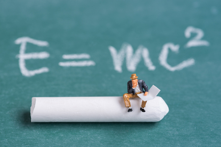 miniature people sitting on chalk stick with the relativity theory background