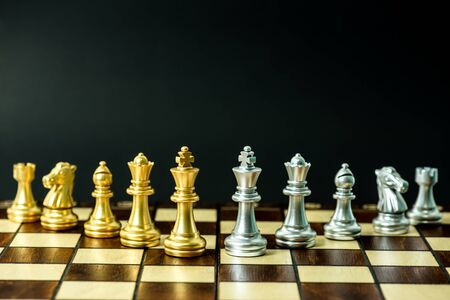 gold and silver chess pieces on a chessboard, business strategy concept