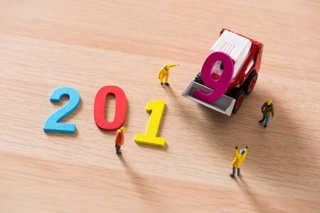 miniature people arrange wood text number 2019 for happy new year