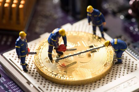 miniature worker cutting bitcoin, halving concept Stock Photo