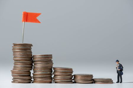 business miniature people walking up to the top stack of coins with red flag on white background Stock Photo