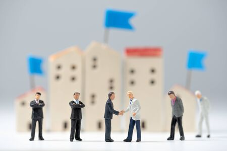 Apretón de manos de personas en miniatura de negocios con un fondo de modelo de casa