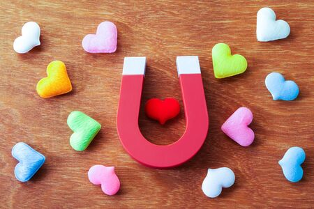magnet gravitate heart shape on wooden background, love concept Reklamní fotografie