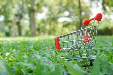 miniature red shopping cart on green garden
