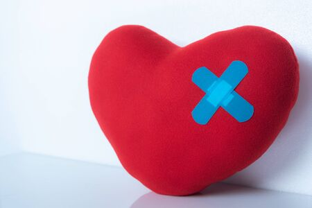 red wound heart with bandage on white background