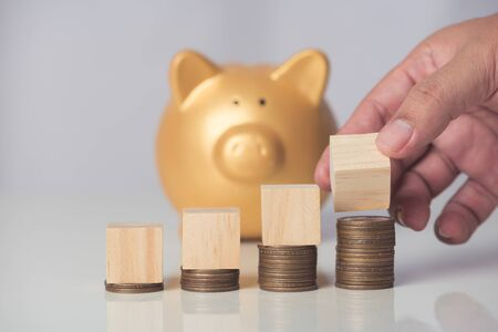 wood cube on coins stack, gold piggy bank background
