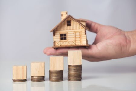 hand holding house  with wood cube on coins stack Banco de Imagens